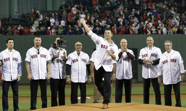 Members of the 2004 World Series Championship Boston Red Sox, including manager Terry Francona, second from right, watch as pitcher Keith Foulke throws a ceremonial first pitch as they are honored at Fenway Park before a baseball game against the Tampa Bay Rays in Boston, Tuesday, Sept. 25, 2012. (AP Photo/Elise Amendola)