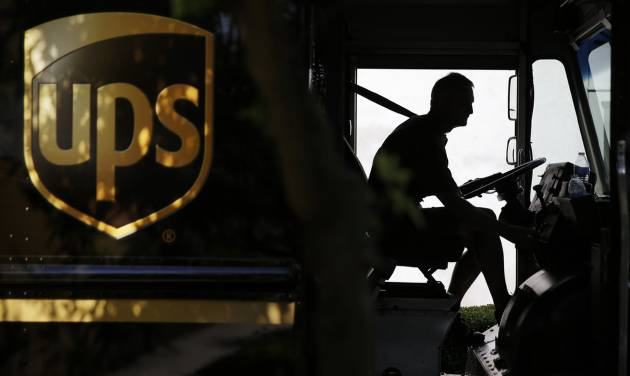 In this June 20, 2014 photo, United Parcel Service driver Marty Thompson starts his truck up after making a delivery in Cumming, Ga.  UPS reports quarterly earnings on Tuesday, July 29, 2014. (AP Photo/David Goldman)