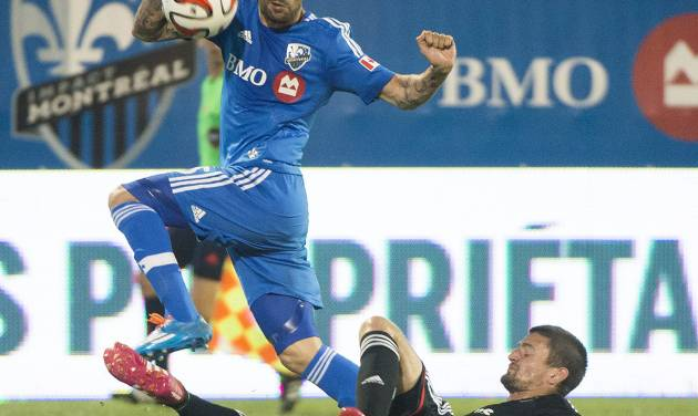 Montreal Impact's Andres Romero, left, and D.C. United's Perry Kitchen battle for the ball during the second half of a soccer game, Wednesday, June 11, 2014 in Montreal. (AP Photo/The Canadian Press, Graham Hughes)