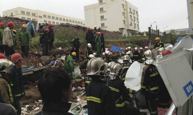 In this photo taken by mobile phone, rescuers and workers conduct a search operation following a wall collapse in Qingdao in east China's Shandong province Sunday, May 11, 2014. The wall collapse triggered by heavy rains at a recycling plant killed 18 people and injured three others early Sunday in the eastern city of Qingdao, state media reported. (AP Photo) CHINA OUT
