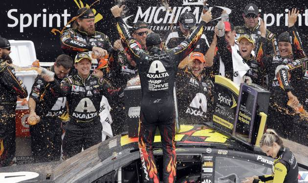 Jeff Gordon celebrates his victory with his crew after the NASCAR Sprint Cup Series Pure Michigan 400 auto race at Michigan International Speedway in Brooklyn, Mich., Sunday, Aug. 17, 2014. (AP Photo/Paul Sancya)