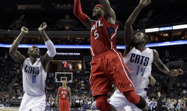 Atlanta Hawks' Josh Smith (5) drives to the basket past Charlotte Bobcats' Michael Kidd-Gilchrist (14) and Bismack Biyombo (0) during the first half of an NBA basketball game in Charlotte, N.C., Wednesday, Jan. 23, 2013. (AP Photo/Chuck Burton)
