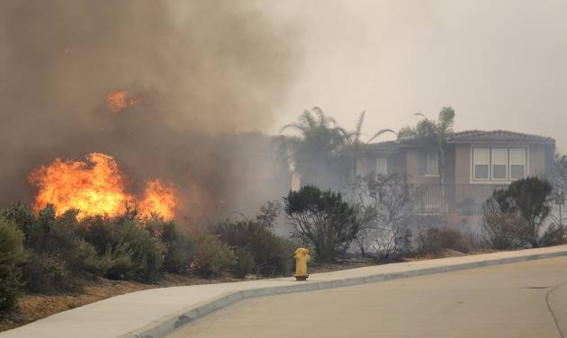 A wildfire climbs a canyon toward homes Wednesday, May 14, 2014, in Carlsbad, Calif. More wildfires broke out Wednesday in San Diego County — threatening homes in Carlsbad and forcing the evacuations of military housing and an elementary school at Camp Pendleton — as Southern California is in the grip of a heat wave. (AP Photo)