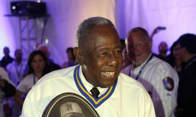 Hank Aaron holds a replica of a plaque that will be displayed on the new Milwaukee Brewers Wall of Honor before a baseball game between the Brewers and the Cincinnati Reds, Friday, June 13, 2014, in Milwaukee. (AP Photo/Morry Gash)