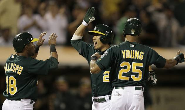 Oakland Athletics' Kurt Suzuki, center, is congratulated by Alberto Callaspo (18) and Chris Young (25) after Suzuki hit a three-run home run off Tampa Bay Rays' David Price in the fifth inning of a baseball game, Friday, Aug. 30, 2013, in Oakland, Calif. (AP Photo/Ben Margot)