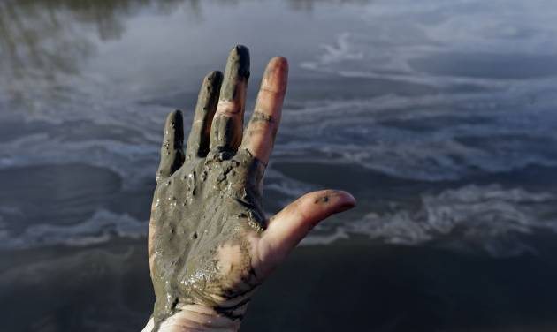Amy Adams, North Carolina campaign coordinator with Appalachian Voices, shows her hand covered with wet coal ash from the Dan River swirling in the background as state and federal environmental officials continued their investigations of a spill of coal ash into the river in Danville, Va., Wednesday, Feb. 5, 2014. Duke Energy estimates that up to 82,000 tons of ash has been released from a break in a 48-inch storm water pipe at the Dan River Power Plant in Eden N.C. on Sunday. (AP Photo/Gerry Broome)