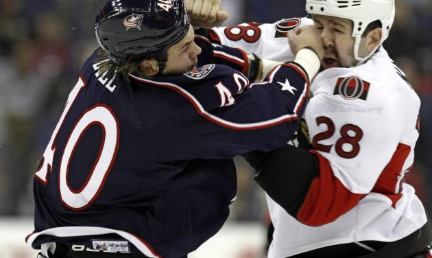 Columbus Blue Jackets' Jared Boll, left, fights Ottawa Senators' Matt Kassian in the first period of an NHL hockey game in Columbus, Ohio, Tuesday, Nov. 5, 2013. (AP Photo/Paul Vernon)