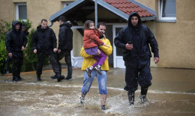 A man evacuates his daughter from their home hit by flood waters as police officers help out in a suburb of Belgrade, Serbia, Thursday, May 15, 2014. Some hundreds of people have been evacuated from their homes as floods caused by heavy rains gripped the Balkans Thursday, overflowing roads, bridges and railways, closing down schools, and cutting off power supplies and phone lines. (AP Photo/Marko Drobnjakovic)