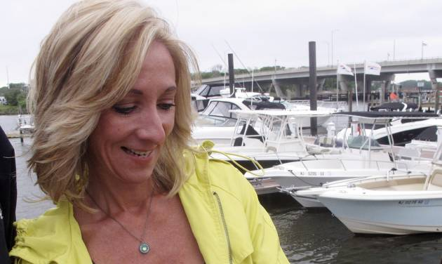 In this photo taken on May 28, 2014, Helen Henderson, a project manager for the American Littoral Society, demonstrates a new smart phone app developed for the group that lets people quickly and easily report water pollution or other marine environmental problems to authorities at a marina in Brick, N.J. The project was paid for by a $325,000 federal grant that came from fines levied on water polluters. (AP Photo/Wayne Parry)
