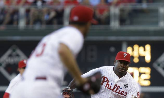 Philadelphia Phillies' Ryan Howard tosses the ball to pitcher Cole Hamels for an out at first on Miami Marlins' Tom Koehler in the third inning of a baseball game, Thursday, June 26, 2014, in Philadelphia. (AP Photo/Laurence Kesterson)