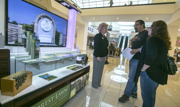 In this photo taken Thursday, Jan. 30, 2014, Forest Lawn regional sales manager Hilda Carabes, left, shows Mark Sanchez and his wife the Forest Lawn stand at the Glendale Galleria mall in Glendale, Calif. Forest Lawn, famous as the final resting place for everyone from Al Jolson to Michael Jackson, has begun staffing outlets at shopping malls, reasoning that planning for death, either for a loved one or yourself, might not be quite as intimidating for some people if it takes place in a lively, happy place like a mall rather than the more somber confines of a cremation home. (AP Photo/Damian Dovarganes)