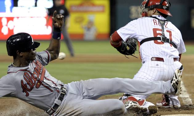 Atlanta Braves' B.J. Upton, left, beats a tag by Philadelphia Phillies' Carlos Rui, right,  and scores on a Tim Hudson single in the fifth inning of a baseball game on Saturday, July 6, 2013, in Philadelphia. (AP Photo/Michael Perez)