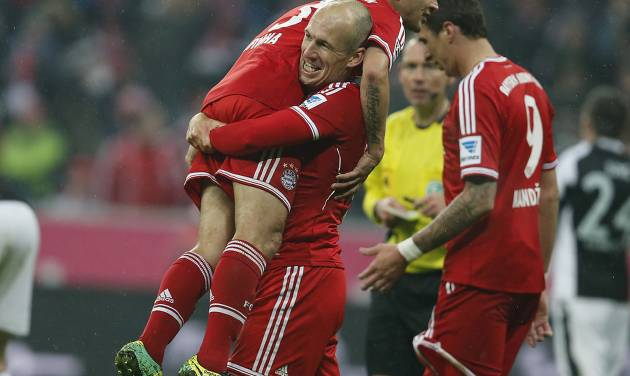 Bayern's Arjen Robben of the Netherlands lifts Bayern's Rafinha of Brazil to celebrate after scoring during the German first division Bundesliga soccer match between Bayern Munich and Eintracht Frankfurt in Munich, Germany, Sunday, Feb. 2, 2014. (AP Photo/Frank Augstein)