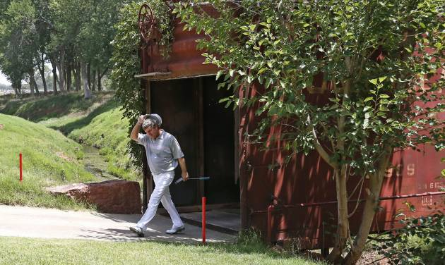 Gene Sauers walks out of an old railroad box car that serves as a bridge during the third round of play at the 2014 U.S. Senior Open golf tournament at Oak Tree National in Edmond, Okla., Saturday, July 12, 2014. Sauers finished the day as the leader. (AP Photo/Sue Ogrocki)
