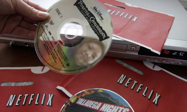 "FILE-In this Jan. 24, 2007 file photo, Netflix customer Carleen Ho holds up DVD movies, ""Talladega Nights"" and ""Pirates of the Caribbean' that she rented from Netflix, at her home in Palo Alto, Calif. Netflix is more popular among couch potatoes than investors a year after its polarizing decision to raise U.S. prices for video subscription services by as much as 60 percent. The unexpected twist that Netflix announced a year ago Thursday, July 12, 2012, triggered mass customer cancellations and a sell-off in its stock that has wiped out more than $11 billion in shareholder wealth. (AP Photo/Paul Sakuma, file)"