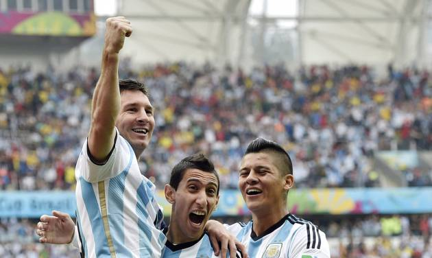 Argentina's Lionel Messi, left, is carried by his teammates Argentina's Angel di Maria (7) and Marcos Rojo (16) after scoring his side's first goal during the group F World Cup soccer match against Nigeria at the Estadio Beira-Rio in Porto Alegre, Brazil, Wednesday, June 25, 2014. (AP Photo/Martin Meissner)