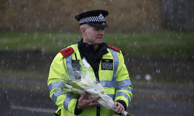A police officer holds a floral tribute handed to him by a member of the public to be placed at the scene of a terror attack in Woolwich, southeast London, Thursday, May 23, 2013. The British government's emergency committee met Thursday after two attackers killed a man in a daylight attack in London that raised fears terrorism had returned to the capital.  (AP Photo/Sang Tan)