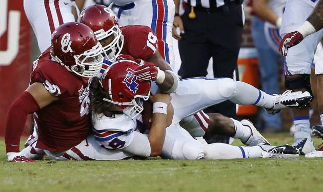 Louisiana Tech quarterback Cody Sokol (19) is sacked by Oklahoma defensive end Matt Dimon (90) and linebacker Eric Striker (19) in the second quarter of an NCAA college football game in Norman, Okla., Saturday, Aug. 30, 2014. (AP Photo/Sue Ogrocki)