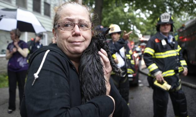 Cindy Piscopo holds her cat Zack after the cat was found by a firefighter after members of his battalion battled a blaze in a series of townhouses, including Piscopo's home in the Staten Island borough of New York, Thursday, June 5, 2014.  About 200 firefighters responded to the blaze that erupted at about 1 a.m. on the island south of Manhattan. They battled the five-alarm fire for several hours. A Fire Department of New York spokesman said 23 firefighters and 11 civilians suffered injuries ranging from minor to serious but none was considered life-threatening. He said the number was expected to climb slightly. (AP Photo/Kathy Willens)