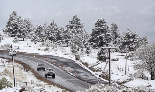 Commuters pass fresh snow from the fringe of a major spring snowstorm in the nearby mountains, in Superior, Colo., on Monday, May 12, 2014. A spring storm has brought up to 3 feet of snow to the Rockies and severe thunderstorms and tornadoes to the Midwest. In Colorado, the snow that began falling on Mother's Day caused some power outages as it weighed down newly greening trees. (AP Photo/Brennan Linsley)