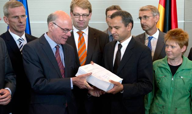 Committee chairman Sebastian Edathy , center right,  and other members of the committee present the final report  of the NSU investigation committee to  parliament president Norbert Lammert, center left,  in Berlin,  Thursday Aug. 22, 2013. The nearly 1,400-page report released Thursday follows a 19-month review of how police and intelligence agencies failed to stop the National Socialist Underground (NSU) group killing eight Turks, a Greek and a policewoman between 2000 and 2007.The group was only linked to the killings after two main members died in a murder-suicide after a botched 2011 bank robbery. The third suspected main member is now on trial. The cross-party committee says authorities didn't properly consider the possibility that the killings were racially motivated, partly because of their own biases. It calls for more minorities in the security services.   (AP Photo/dpa, Rainer Jensen)