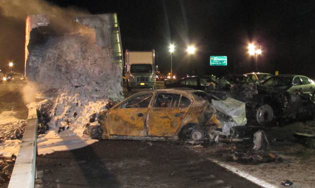 A tractor-trailer still smolders hours after a chain-reaction crash on the Long Island Expressway on Wednesday, Dec. 19, 2012 in Shirley, N.Y. At least one person was killed and 32 others were injured in the pileup, which involved about two dozen vehicles. (AP Photo/Frank Eltman)