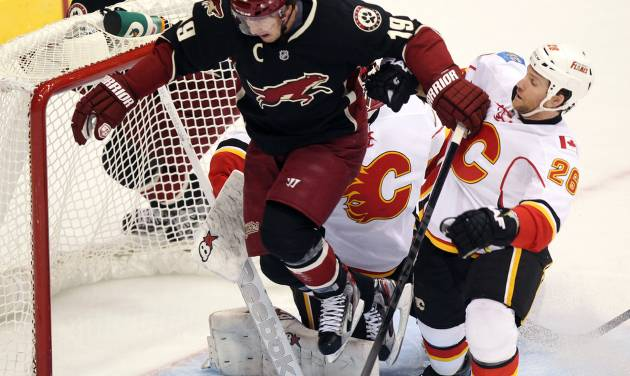 Phoenix Coyotes right winger Shane Doan (19) leaps over Calgary Flames goalie Daniel Taylor, rear, of Great Britain, while being checked by defenseman Dennis Wideman (26) in the second period of an NHL hockey game, Monday, Feb. 18, 2013, in Glendale, Ariz. (AP Photo/Paul Connors)