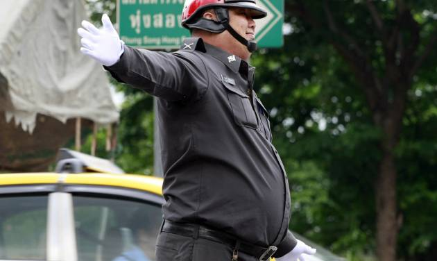 In this photo taken Thursday, July 4, 2013, an overweight traffic police officer Sgt. Wanchat Wongnothong performs his duty on a street in Bangkok, Thailand. As part of a national effort to reduce the numbers of overweight officers, Thailand has opened a 12-day boot camp to get police into shape. This week, 60 overweight officers from around the country were sent to a police training center for dawn-to-dusk exercise and lecture programs on living more healthy. (AP Photo/Apichart Weerawong)