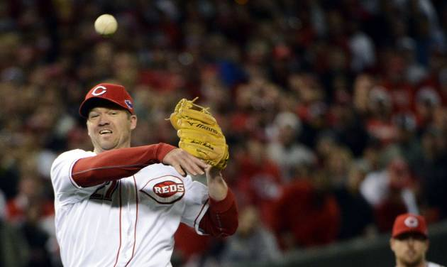 Cincinnati Reds third baseman Scott Rolen throws to first base after fielding a ground ball hit by San Francisco Giants' Joaquin Arias in the 10th inning during Game 3 of the National League division baseball series, Tuesday, Oct. 9, 2012, in Cincinnati. Rolen was charged with an error on the play allowing Buster Posey to score. The Giants won 2-1 in the 10th inning to cut their playoff deficit to 2-1. (AP Photo/Michael Keating)