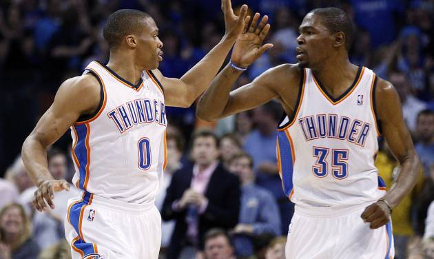Oklahoma City Thunder guard Russell Westbrook (0) and forward Kevin Durant (35) exchange high-fives following a basket by Westbrook in the second quarter of an NBA basketball game against the Chicago Bulls in Oklahoma City, Sunday, April 1, 2012. (AP Photo/Sue Ogrocki)