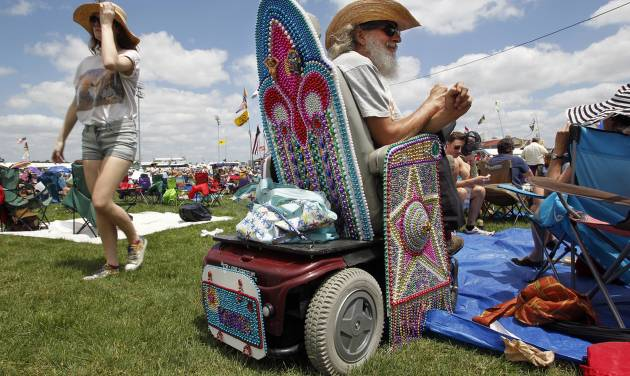 David Metzenthin, of Kansas, who has to get around by wheelchair, gets into the New Orleans spirit by covering his wheelchair with Mardi Gras beads for the New Orleans Jazz & Heritage Festival presented by Shell on Friday, April 27, 2012.(AP Photo/The Times-Picayune, Chris Granger) MAGS OUT; NO SALES; USA TODAY OUT