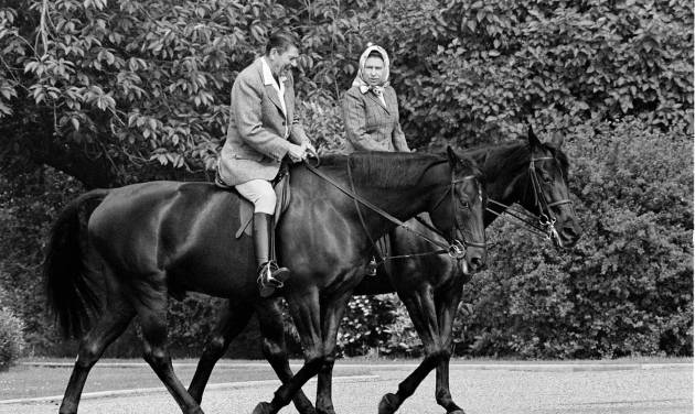 FILE - In this June 8, 1982 file photo, U.S. President Ronald Reagan, on Centennial, and Britain's Queen Elizabeth II, on Burmese, go horseback riding on the grounds of Windsor Castle, England. It is not often that the president of the United States needs to seek fashion advice. But when Ronald Reagan was getting ready for a visit to England as a guest of Queen Elizabeth II in June 1982, his people had an important question for the Brits: Just what does one wear to go riding with the queen in the magnificent horse country surrounding Windsor Castle? The answer: Something smart, but casual, of course. Riding boots, breeches and a turtleneck sweater would do fine _ no need for formal riding attire.  The fashion inquiry is but one tidbit contained in nearly 500 pages of formerly Confidential documents relating to the Reagan visit being made public Friday, Dec. 28, 2012 by Britain's National Archives. (AP Photo/Bob Daugherty, File)