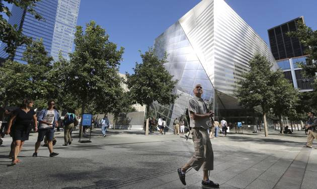 A visitor to the National September 11 Memorial and Museum takes in the sight as he walks past the museum, Friday, Sept. 6, 2013 in New York. Construction is racing ahead inside the museum as the 12th anniversary of the Sept. 11, 2001 attacks draws near. Several more large artifacts have been installed in the cavernous space below the World Trade Center memorial plaza. (AP Photo/Mary Altaffer)