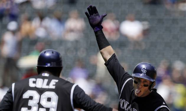 Colorado Rockies' Troy Tulowitzki (2) celebrates a solo home run with third base coach Stu Cole (39) during the first inning of a baseball game against the San Diego Padres on Wednesday, July 9, 2014, in Denver. (AP Photo/Jack Dempsey)