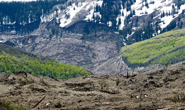 The results of a three-mile long mudslide are piled below Grand Mesa, where the slide started, background, in a remote part of western Colorado near the small town of Collbran Monday, May 26, 2014. Rescue teams are searching for three men missing after a half-mile stretch of a ridge saturated with rain collapsed. (AP Photo/Grand Junction Daily Sentinel, Dean Humphrey)