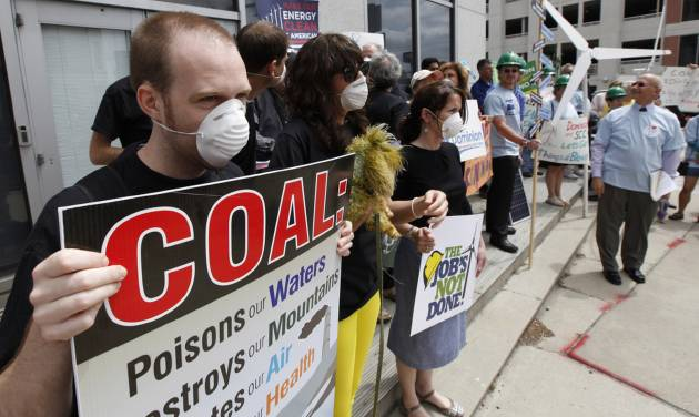 Environmental activists carry signs and wear dust masks as they protest outside the State Corporations Commission in Richmond, Va., Tuesday, May 8, 2012. Dominion Virginia power presented its long term energy plans to state regulators. (AP Photo/Steve Helber)