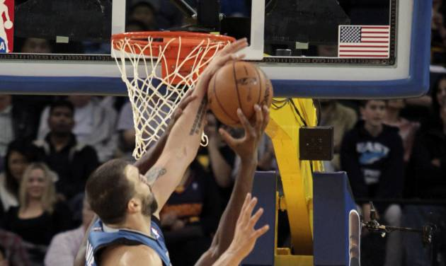 Minnesota Timberwolves' Nikola Pekovic, of Montenegro, blocks the shot of Golden State Warriors' Festus Ezeli (31) in the first quarter of an NBA basketball game in Oakland, Calif., Saturday, Nov. 24, 2012. Watching at right is Timberwolves' Kevin Love (42). (AP Photo/Mathew Sumner)