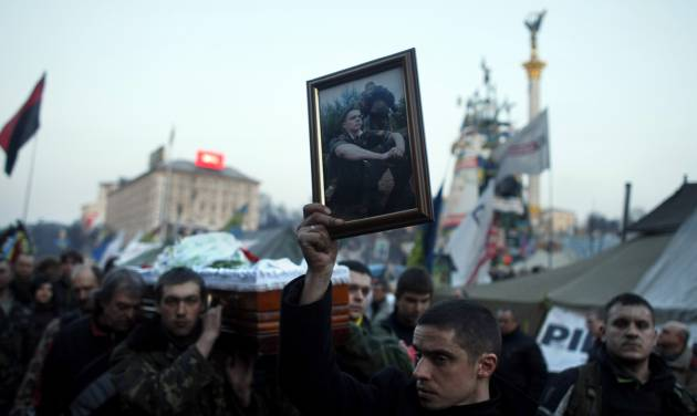 A man carries a photo of an anti-government protester killed in clashes with the police, during a funeral procession at Independence Square in Kiev, Ukraine, Friday, Feb. 21, 2014. In a day that could significantly shift Ukraine's political destiny, opposition leaders signed a deal Friday with the country's beleaguered president that calls for early elections, a new constitution and a new unity government. (AP Photo/ Marko Drobnjakovic)