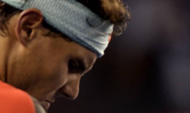 Rafael Nadal of Spain looks at the bandaged blister on his left hand as he plays Roger Federer of Switzerland during their semifinal at the Australian Open tennis championship in Melbourne, Australia, Friday, Jan. 24, 2014.(AP Photo/Andrew Brownbill)