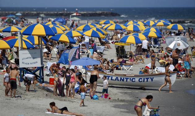 In this Wednesday, July 23, 2014 photograph people relax and play in the ocean in Atlantic City, N.J. Good weather and greater awareness that the Jersey shore has made huge strides in recovering from Superstorm Sandy helped make the second summer after the storm better than the first one, many shore merchants and elected officials say. Some business owners report profits up 20 to 30 percent in the summer of 2014 compared with 2013, when the shore was still in the early stages of recovering from the devastating Oct. 29, 2012, storm. (AP Photo/Mel Evans)