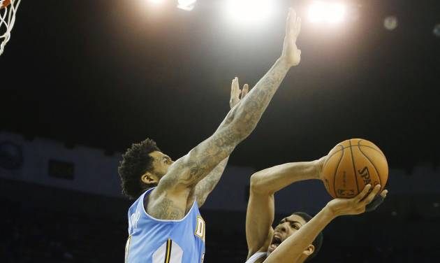 New Orleans Pelicans power forward Anthony Davis (23) shoots around Denver Nuggets small forward Wilson Chandler (21) in overtime in an NBA basketball game in New Orleans, Sunday, March 9, 2014. The Pelicans defeated the Nuggets 111-107. (AP Photo/Bill Haber)