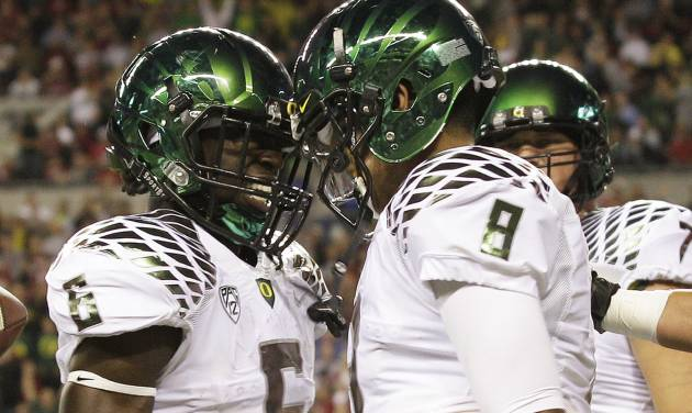 Oregon quarterback Marcus Mariota, right, celebrates his first half touchdown against Washington State with Oregon's De'Anthony Thomas, left, during an NCAA college football game, Saturday, Sept. 29, 2012, in Seattle. Oregon beat Washington State, 51-26. (AP Photo/Ted S. Warren)