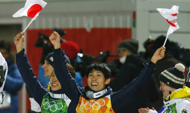 Japan's Taku Takeuchi, left, and Daiki Ito celebrate winning the bronze as Germany's Marinus Kraus, right, applauds after  the ski jumping large hill team competition at the 2014 Winter Olympics, Monday, Feb. 17, 2014, in Krasnaya Polyana, Russia. (AP Photo/Dmitry Lovetsky)