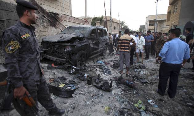 Security forces inspect the scene of a car bomb attack in Basra, 340 miles (550 kilometers) southeast of Baghdad, Iraq, Sunday, July 14, 2013. A wave of explosions tore through overwhelmingly Shiite cities south of Baghdad shortly before the Muslim faithful broke their Ramadan fasts, killing tens of people and wounding dozens, according to officials. The bombings are part of a sudden surge of violence that has brought Iraq to the brink of all-out sectarian conflict. (AP Photo/ Nabil al-Jurani)