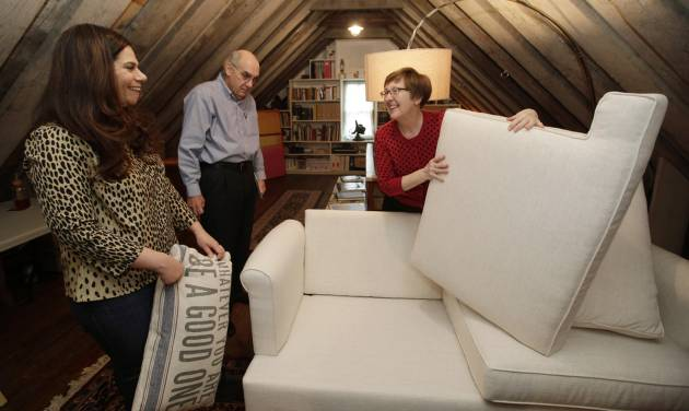 In this Sunday, Jan. 12, 2014, photo, Rebecca Gwynne, left, of Tuckahoe, N.Y., reacts as Marijane Hamren inspects Gwynne's Simplicity Sofa with her husband Jim Hamren, in Tuckahoe, N.Y.  While Simplicity's furniture is sold only over the Internet, some customers want to see and try out the sofas and chairs. Owner Jeff Frank contacts people who have already bought his furniture, and asks them if they'll let a prospective customer stop by to take a look. (AP Photo/Kathy Willens)