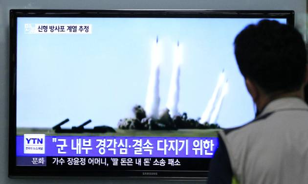 """A man watches a TV news program showing the missile launch conducted by North Korea, at Seoul Railway Station in Seoul, South Korea, Thursday, June 26, 2014. North Korea fired three short-range projectiles Thursday into the waters off its east coast, a South Korean defense official said. The move was most likely a routine test-firing, but the official said it could also be meant to stoke tensions with Seoul. The writing on tje screen reads """"The missiles were launched to alert and express its internal solidarity."""" (AP Photo/Ahn Young-joon)"""