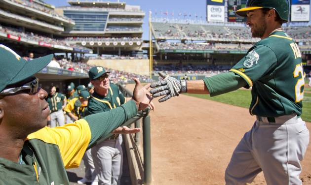 Oakland Athletics left fielder Sam Fuld, right, is congratulated after hitting a home run against the Minnesota Twins in the fourth inning of a baseball game on Thursday, April 10, 2014 in Minneapolis.(AP Photo/Andy Clayton-King)