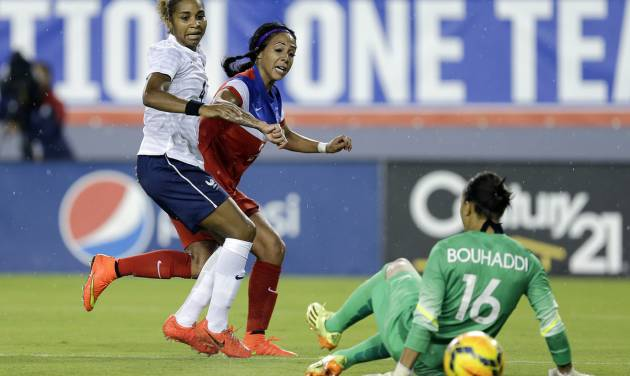 United States forward Sydney Leroux, center, scores past France goalkeeper Sarah Bouhaddi (16) and defender Laura Georges (4) during the first half of a women's friendly soccer match on Saturday, June 14, 2014, in Tampa, Fla. (AP Photo/Chris O'Meara)