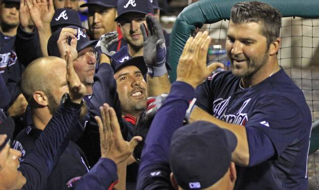 Atlanta Braves' Dan Uggla, right celebrates with his teammates after he hit a grand slam against the Philadelphia Phillies in the ninth inning of a baseball game Monday, April 14, 2014, in Philadelphia. Atlanta won 9-6.  (AP Photo/H. Rumph Jr)