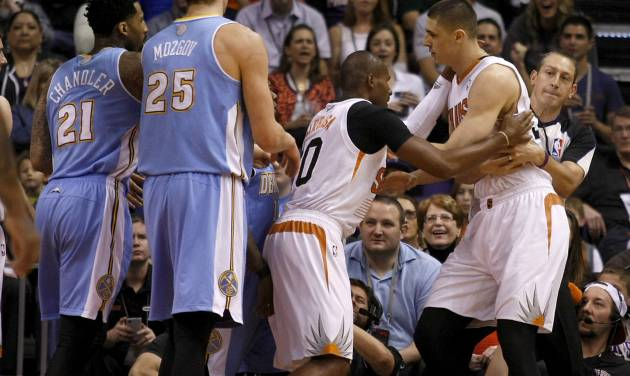 Phoenix Suns center Alex Len (21) gets held back from Leandro Barbosa (10) after getting into a shoving match with players of the Denver Nuggets in the first quarter during an NBA basketball game, Sunday, Jan. 19, 2014, in Phoenix. (AP Photo/Rick Scuteri)